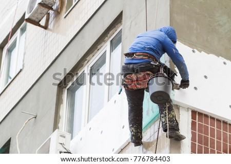 Thermal insulation of the exterior wall panel. Worker man insulates wall high-rise building