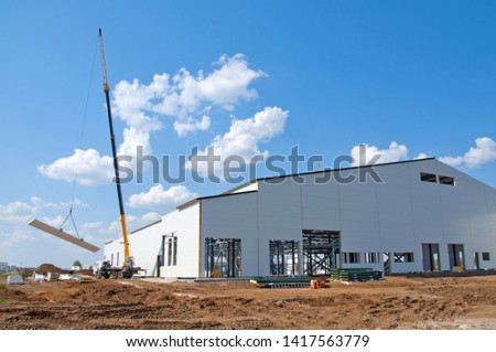 Thermal insulation of the metal frame of the building with insulation panels. The process of installing insulation panels. Modern building insulation.