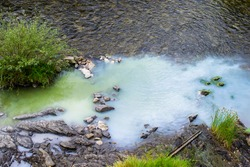 Thermal, sulphurous water flowing into the river. The water is whitish