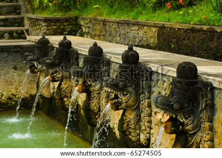 Thermal water is released from the mouth of statues at a hot springs in Banjar, Bali, Indonesia - stock photo