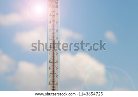 Thermometer against a blue sky with clouds, a concept of hot weather. Above 30 degrees Celsius
