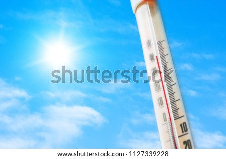Thermometer against the background of an blue hot glow of clouds and sun, concept of hot weather. Above 40 degrees Celsius
