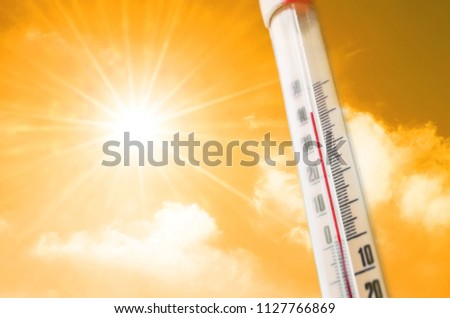 Thermometer against the background of an orange yellow hot glow of clouds and sun, concept of hot weather.  Above 40 degrees Celsius