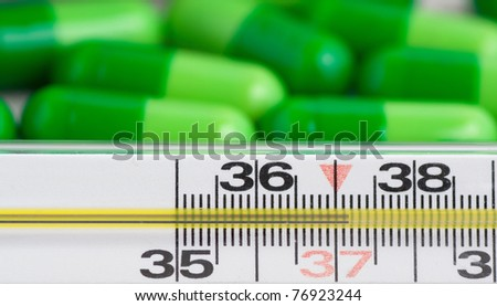 Thermometer and pills on white