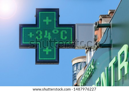 Thermometer in green pharmacy screen sign displays extremely hot temperature of 34 degrees Celsius during heatwave / heat wave in summer in Belgium
