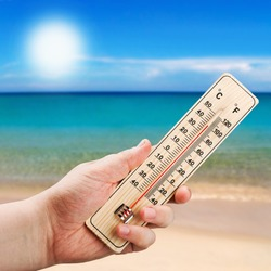 Thermometer in hand shows the intense heat on the background of the sea
