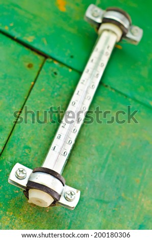 thermometer on a green background outdoors