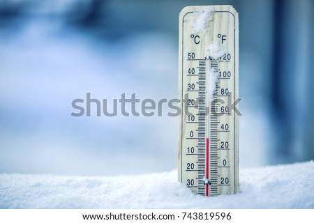 Thermometer on snow shows low temperatures - zero. Low temperatures in degrees Celsius and fahrenheit. Cold winter weather - zero celsius thirty two  farenheit.