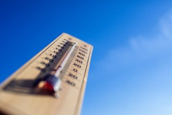 Thermometer on the blue sky background. Weather forecast and outdoor temperature concept