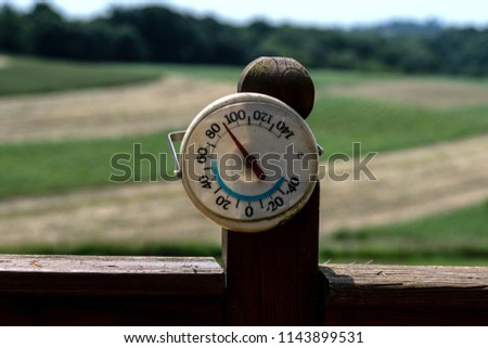 Thermometer reading 90 degrees Fahrenheit with out of focus corn and hay fields in the background in rural Appalachia