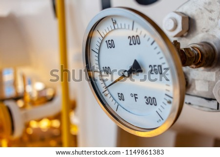 Thermometer, Temperature gauge or temperature indicator reading seventy five Fahrenheit (°F) in offshore oil and gas refinery process operation industry.