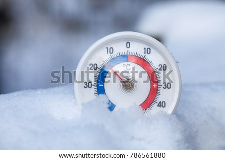 Thermometer with celsius scale placed in a fresh snow showing sub-zero temperature minus fifteen degree a cold winter weather concept