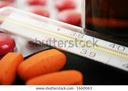 Thermometer with medication. Focus on thermometer