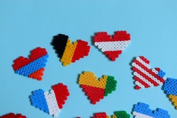 Thermomosaic ready-made figurines in the form of hearts for coloring different flags of countries on a blue background selective focus.