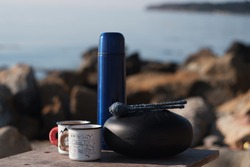 thermos and camping mugs on the background of the sea, homemade tank drum, hank drum
