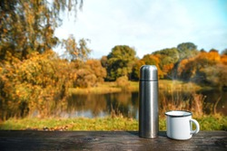 Thermos with a mug on a wooden table. Close up, copy space. The concept of a picnic in nature, travel to the wild. Autumn forest background, yellow, red trees. Wild lake