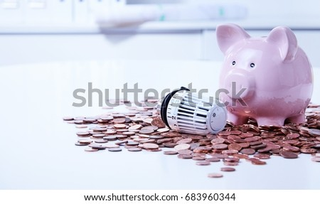 Thermostatic radiator valve with ceramic piggy bank among pile of saved coins #683960344