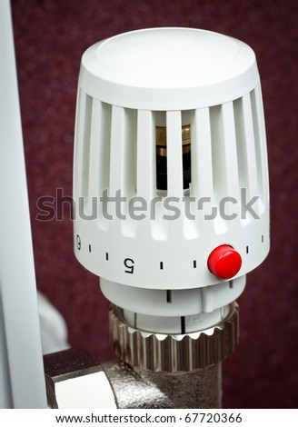 Thermostatic radiator valve with red economy button close-up