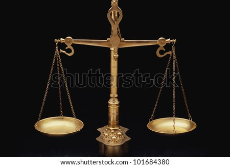 These are the golden scales of justice. They represent the legal systems and courts. These scales are shown in perfect balance against a black background.