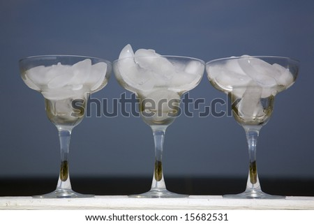 These are three goblets filled with ice sitting on a rail at the ocean front on a very hot summer day.