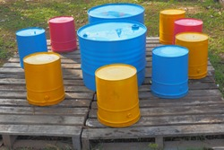 These barrels and paint buckets are painted and set as outdoor seating.  Wooden pallets are used as seating platforms.  Recycling ideas.