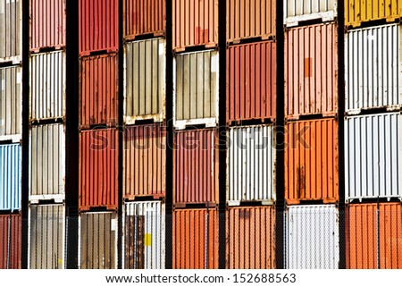 These cargo containers are stacked inside a security barbed wire fence. - stock photo