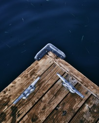 These cleats act like jewelry on this rustic wooden dock. surrounded by deep blue water this evokes calmness