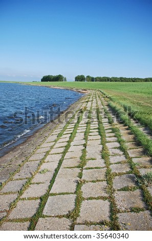 These concrete stones on a dutch dike in  nature reserve Oosterschelde with natural vegetation will be replaced  by a stronger safer material to protect the land against the  rising od the sea level