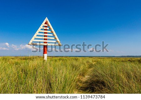 These Signs (German: Bake) on the Ellenbogen Beach mark the border between Germany and Denmark in the Wadden Sea. There are corresponding markings on the Danish mainland.