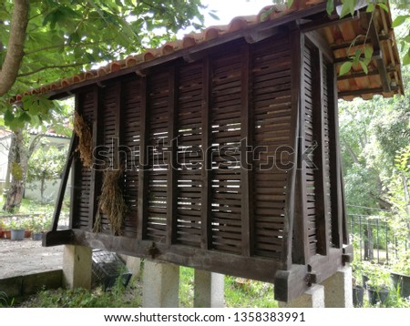 These structures are built above ground and are supported by wooden stilts. A circular stone slab, forming an overhang, is intercalated between the stilts and the granary to prevent rodents from gain. #1358383991