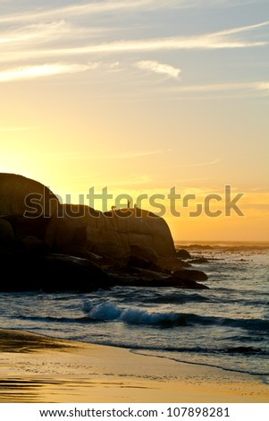These three men are fishing on the rocks in sunset.