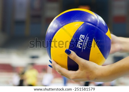 THESSALONIKI, GREECE - FEBRUARY 5, 2015 : Closeup of hands holding a volleyball ball during the Hellenic Volleyball League game Paok vs Aris at PAOK Sports Arena.