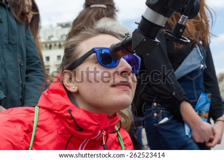 THESSALONIKI, GREECE, MARCH 20, 2015: People watch through a telescope into the sky at a partial solar eclipse. Over Greece  the moon was scheduled to cover approximately 45%
