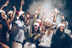 They love Christmas. Group of beautiful young people in Santa hats throwing colorful confetti and looking happy