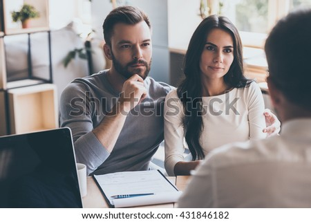 They need an expert advice. Confident young couple listening to some man sitting in front of them at the desk