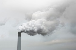Thick and heavy smoke coming out of a huge and high chemical factory chimney under a misty and rainy sky