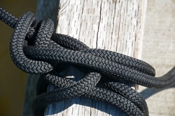 Thick black commercial marine rope tied up to moorage.