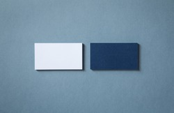 Thick blank double-sided business cards with textured surface stacked up on a grey background