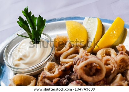 Thick calamari rings served with sauce and lemons.