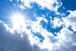 Thick clouds in a Sunny blue sky. The bright sun is peeking out visible through thick dense clouds