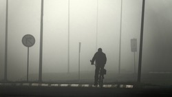 Thick cold autumn winter fog on highway. The cyclist is badly visible in fog