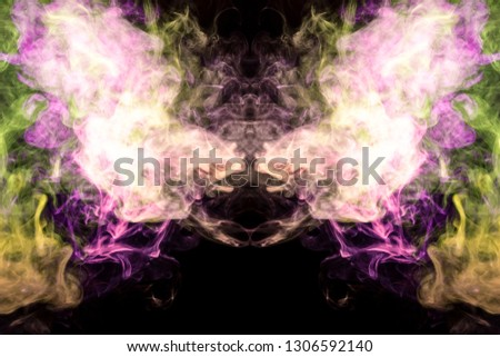 Stock Photo Thick colorful smoke of green pink in the form of a skull, monster, dragon on a black isolated background. Background from the smoke of vape. Mocap for cool t-shirts