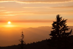 Thick layers of smoke from a nearby forest fire turn the suns rays a glowing orange as it sets over the high Cascade Mountains near Prospect, Oregon with silhouetted fir trees.