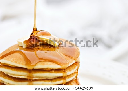 Thick maple syrup pouring onto a stack of fresh pancakes. Shallow depth of field with selective focus on butter.
