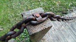 thick metal chain attached to wooden pole