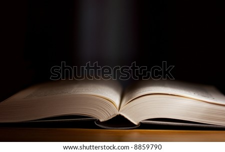 Thick open book in a dark room
