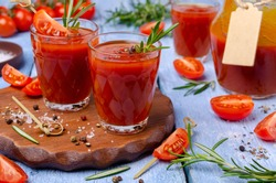 Thick red juice in glass with vegetables and spices on a wooden background. Selective focus.