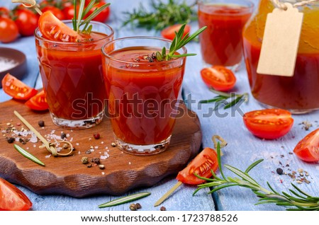 Photo of  Thick red juice in glass with vegetables and spices on a wooden background. Selective focus.