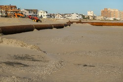 Thick rusty pipeline on a sandy beach forming a right angle