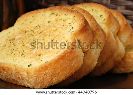 Thick slices of freshly baked garlic bread seasoned with butter and herbs.  Macro with extremely shallow dof.